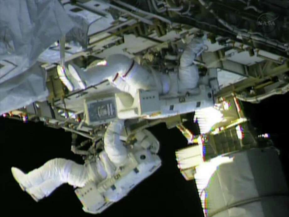 Astronauts Christopher Cassidy (top) and Thomas Marshburn finish work on repairs to the International Space Station. A pump was replaced after an ammonia leak was discovered Thursday. Photo: NASA TV / Getty Images