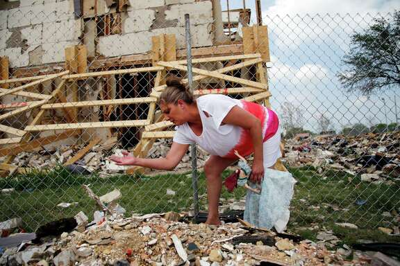 Carol Bare looks through rubble on Friday to find any of her sister Shona Jupe's belongings in West.