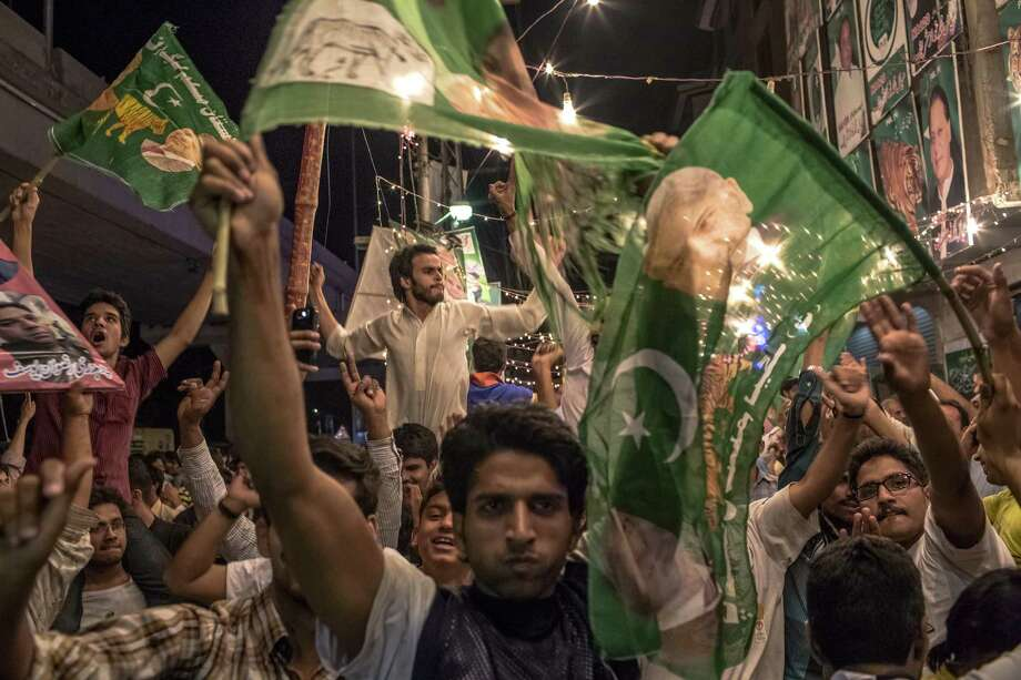 Supporters of Pakistan Muslim League-N (PMLN) celebrate election results in front of a party office late Saturday evening in Lahore, Pakistan, after millions of Pakistanis cast their votes. Photo: Daniel Berehulak / Getty Images