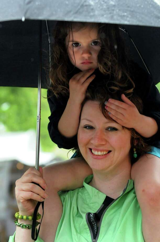 Tricia Hartnett of Voorheesville shares an umbrella with her daughter Madelyn Spath, 4, during the Tulip Festival on Saturday, May 11, 2013, at Washington Park in Albany, N.Y. (Cindy Schultz / Times Union) Photo: Cindy Schultz / 00022344A