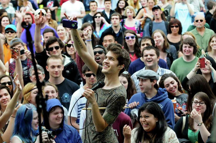 Gary Larsen of Royal Teeth, center, takes a picture using an audience member's camera during their performance on the main stage at the Tulip Festival on Saturday, May 11, 2013, at Washington Park in Albany, N.Y. (Cindy Schultz / Times Union) Photo: Cindy Schultz / 00022344A