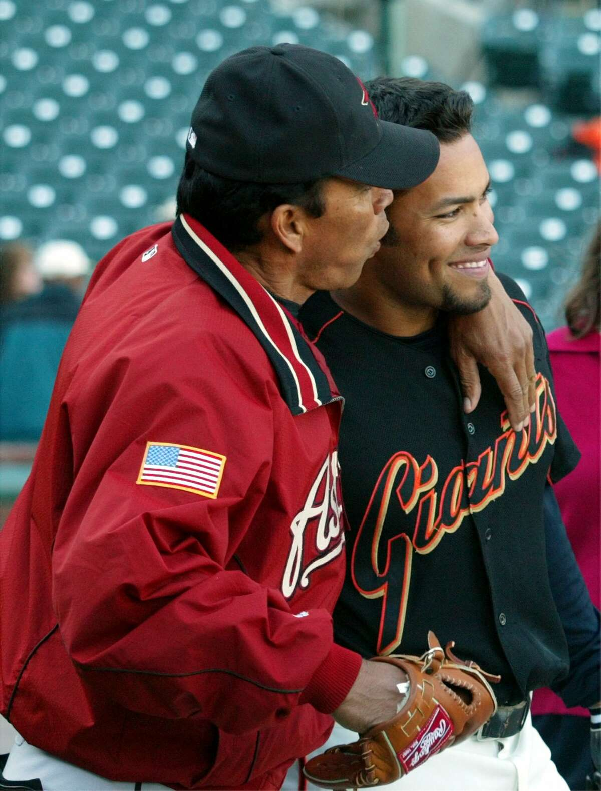 Astros coach Jose Cruz, left, shows a little fatherly affection to his son, San Francisco Giants right fielder Jose Cruz Jr., right, prior to their game in San Francisco in April 2003. The younger Cruz competed at Rice but left after his junior year for the majors. He and his brother Jose Enrique received their degrees from Rice on Saturday.