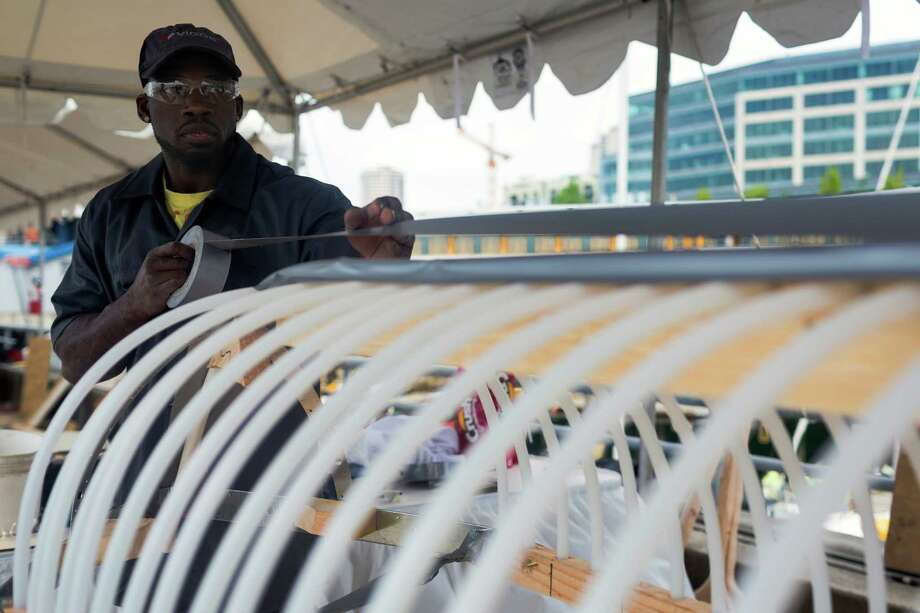 Vigor teammates work to finish their homemade boat before the WorkBoat World Invitational Boatbuilding Competition on the final day of the annual Seattle Maritime Festival Saturday, March 11, 2013, on Pier 66 in Seattle. The four-day festival included a clam chowder cook off, tugboat races and boatbuilding competitions. Photo: JORDAN STEAD, SEATTLEPI.COM / SEATTLEPI.COM