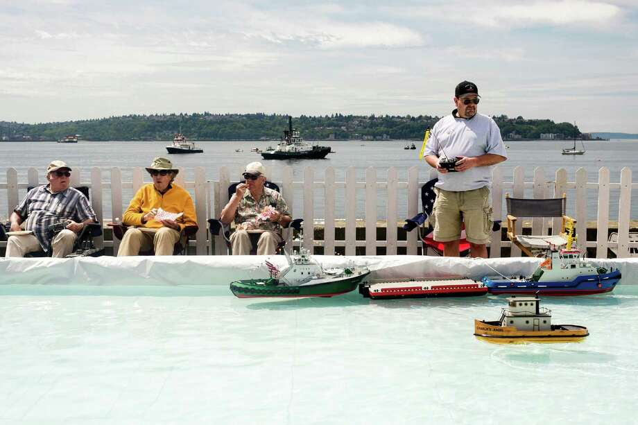 At an RC boat station, Keith Schermerhorn, right, controls a number of handmade, battery-powered miniature models on the final day of the annual Seattle Maritime Festival Saturday, March 11, 2013, on Pier 66 in Seattle. The four-day festival included a clam chowder cook off, tugboat races and boatbuilding competitions. Photo: JORDAN STEAD, SEATTLEPI.COM / SEATTLEPI.COM