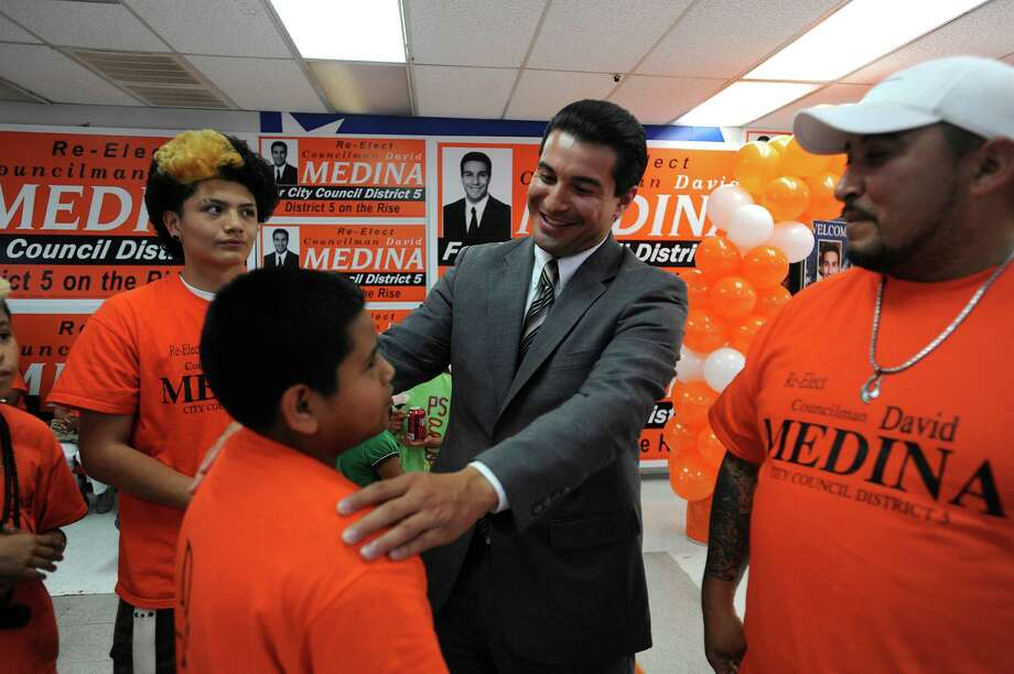 Incumbent District 5 Councilman David Medina greets Mark Lopez, 12, and others at his campaign headquarters on Saturday evening, May 11, 2013. Photo: Billy Calzada, San Antonio Express-News / San Antonio Express-News