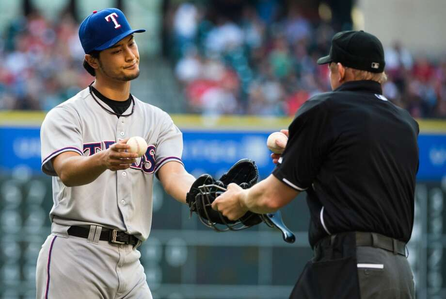 Rangers pitcher Yu Darvish gets a new ball from an umpire.