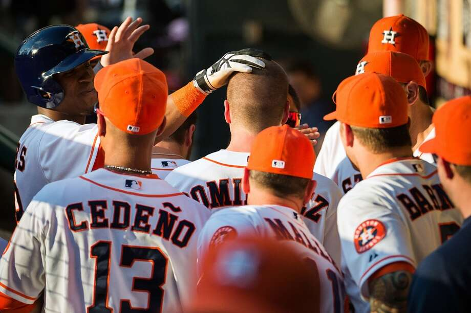 Astros third baseman Matt Dominguez is mobbed by teammates in the dugout after hitting a home run.