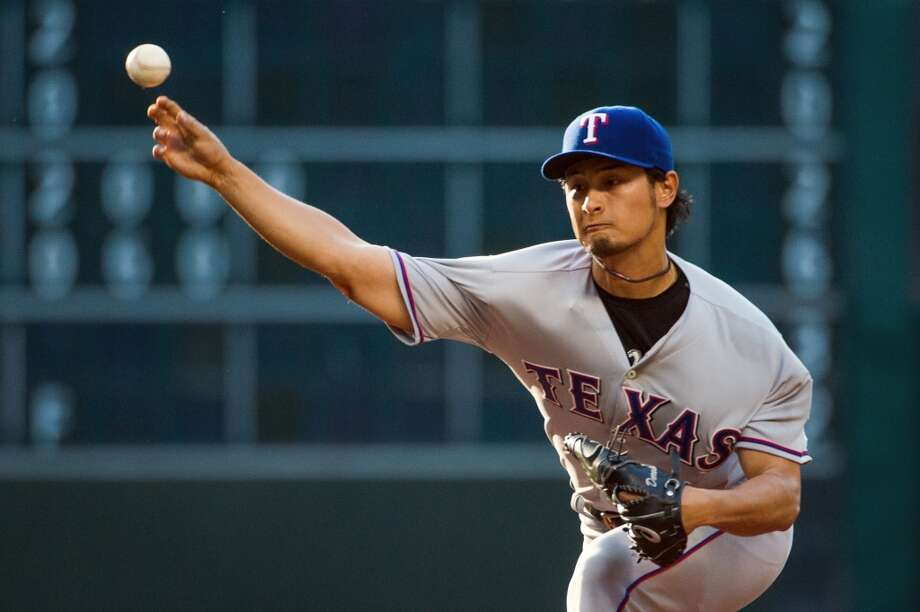 Rangers pitcher Yu Darvish delivers a pitch during the first inning against the Astros.