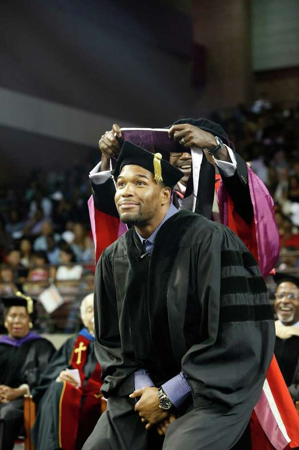 Michael Strahan, who is 6 feet 5, crouches so that Dr. Sunny Ohia, TSU vice president for academic affairs, can do the honors Saturday. Photo: Eric Kayne / 2013 Eric Kayne