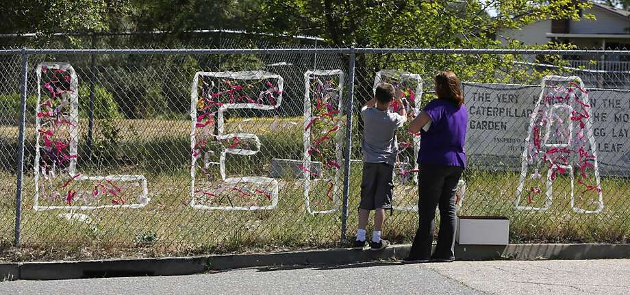 Teacher Cecilia Richardson helps a student tie a ribbon honoring murder victim, third grader Leila Fowler, at Jenny Lind Elementary School in Valley Springs, Calif., Monday April 29, 2013. Authorities are searching for the killer of  Fowler, 8, who was found murdered by her 12-year-old brother in the family's Valley Springs home Saturday. (AP Photo/Rich Pedroncelli) Photo: Rich Pedroncelli, Associated Press