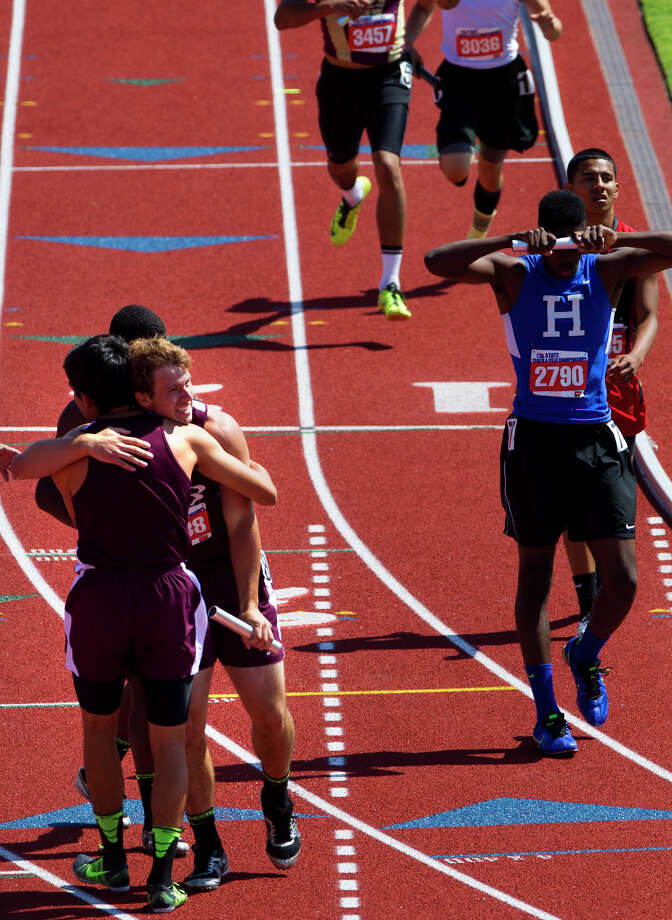 East Bernard's Ty Slanina receives a hug after winning the 2A Boys 4x400 Meter Relay to the finish line during the UIL High School State Track Meet at Mike A. Myers Stadium Saturday, May 11, 2013, in Austin. Photo: Cody Duty, Houston Chronicle / © 2013 Houston Chronicle