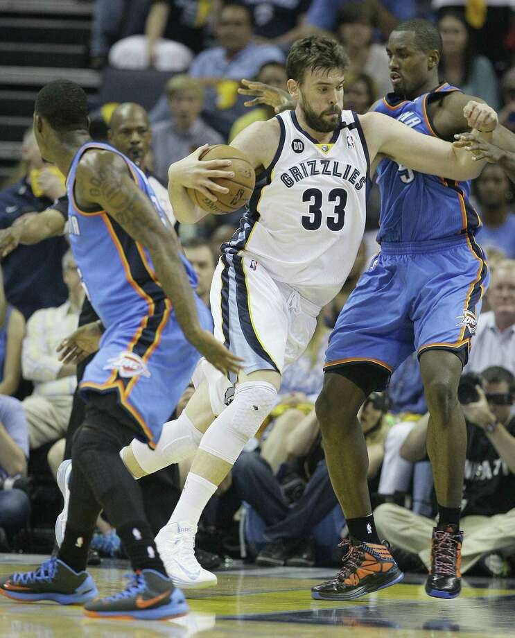Grizzlies center Marc Gasol charges between the Thunder's DeAndre Liggins (left) and Serge Ibaka in the first half of Game 3. Gasol had 20 points. Photo: Danny Johnston / Associated Press