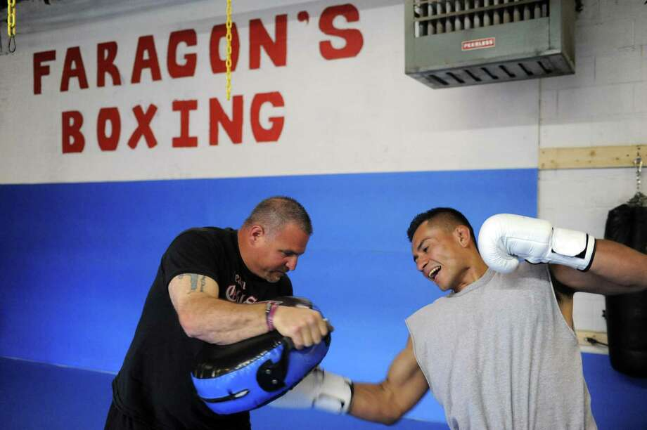 Andy Faragon, a professional MMA fighting coach, works with fighter Marvin Zapata on Wednesday May 8, 2013 in Latham, N.Y. (Michael P. Farrell/Times Union) Photo: Michael P. Farrell