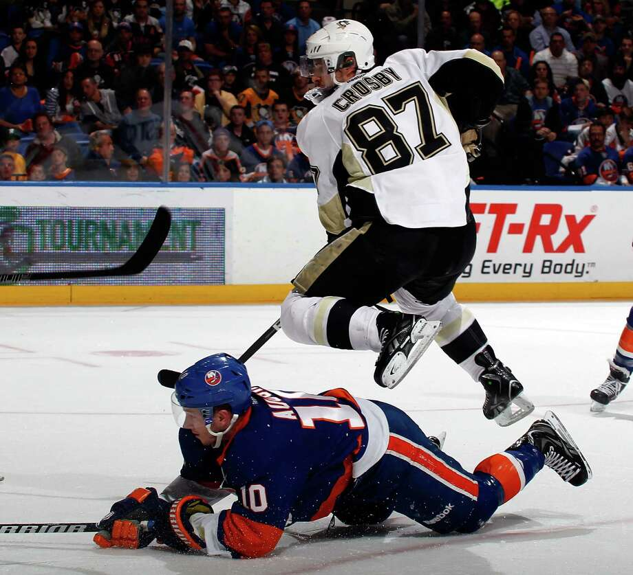 UNIONDALE, NY - MAY 11:  Sidney Crosby #87 of the Pittsburgh Penguins leaps over Keith Aucoin #10 of the New York Islanders as he chases the puck during the third period in Game Six of the Eastern Conference Quarterfinals during the 2013 NHL Stanley Cup Playoffs at Nassau Veterans Memorial Coliseum on May 11, 2013 in Uniondale, New York.  (Photo by Paul Bereswill/Getty Images) Photo: Paul Bereswill