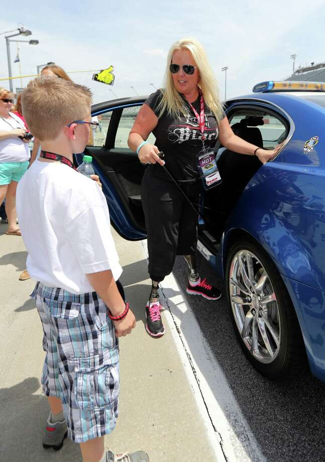 Stephanie Decker, right, talks with her son Dominick, 10, after going around the track before the start the of NASCAR Sprint Cup series auto race at Darlington Raceway, Saturday, May 11, 2013, in Darlington, S.C.  Decker was honored by NASCAR and taken on a  pace car lap after losing her legs protecting her children during a tornado in Indiana on March 3, 2012.  (AP Photo/Mic Smith) Photo: MIC SMITH