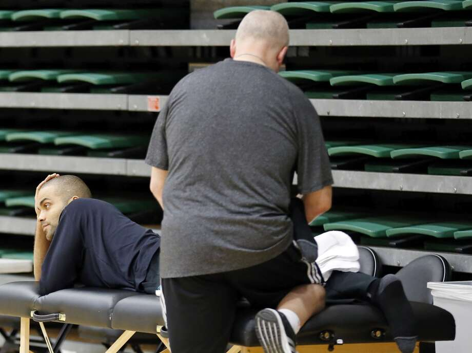 The Spurs' Tony Parker has his left leg worked on during practice Saturday, May 11, 2013, at the War Memorial Gymnasium on the University of San Francisco campus in San Francisco, Calif.