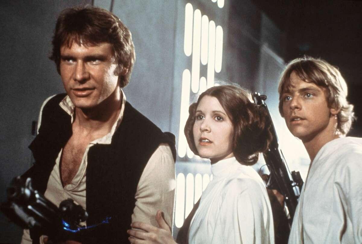 Esta imagen publicitaria difundida por la 20th Century-Fox Film Corporation muestra, de izquierda a derecha, a Harrison Ford como Han Solo, Carrie Fisher en el papel de la princesa Leia Organa y Mark Hamill como Luke Skywalker en una escena de la película