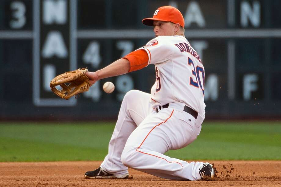 A single off the bat of Rangers outfielder Jeff Baker gets past Astros third baseman Matt Dominguez during the fifth inning.