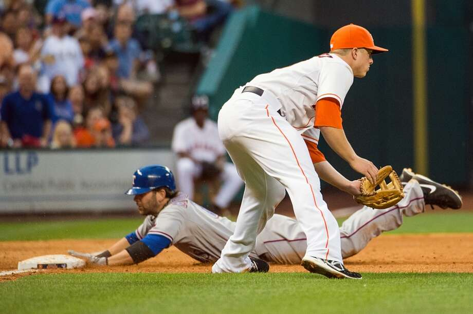 Rangers first baseman Mitch Moreland is safe at third base with a triple as Astros third baseman Matt Dominguez waits for the throw during the sixth inning.
