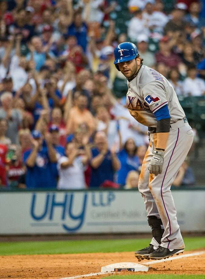 Rangers first baseman Mitch Moreland hops on the base after hitting a triple.