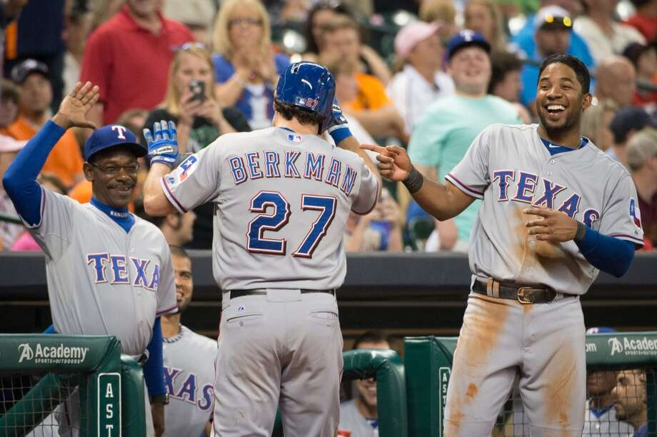 Rangers designated hitter Lance Berkman celebrates with manager Ron Washington, left, and shortstop Elvis Andrus after hitting a home run during the seventh inning. Photo: Smiley N. Pool, Houston Chronicle