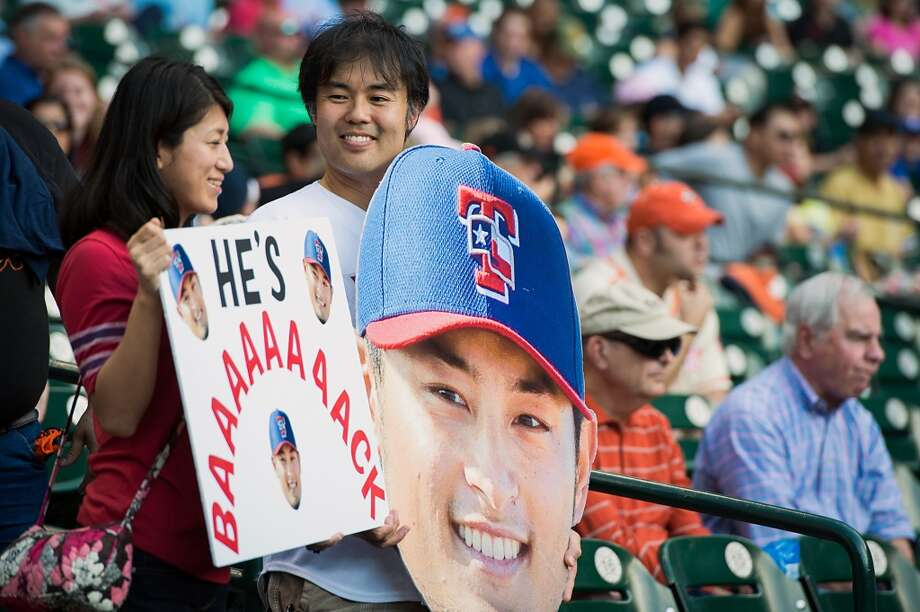 Fans of Rangers starting pitcher Yu Darvish hold signs before the game. Darvish came within one out of a perfect game in his last start in Houston.