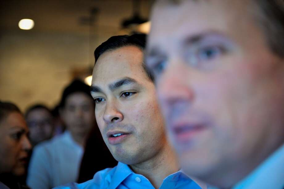 Mayor Julian Castro watches election night voting returns with campaign manager Christian Archer Saturday evening.