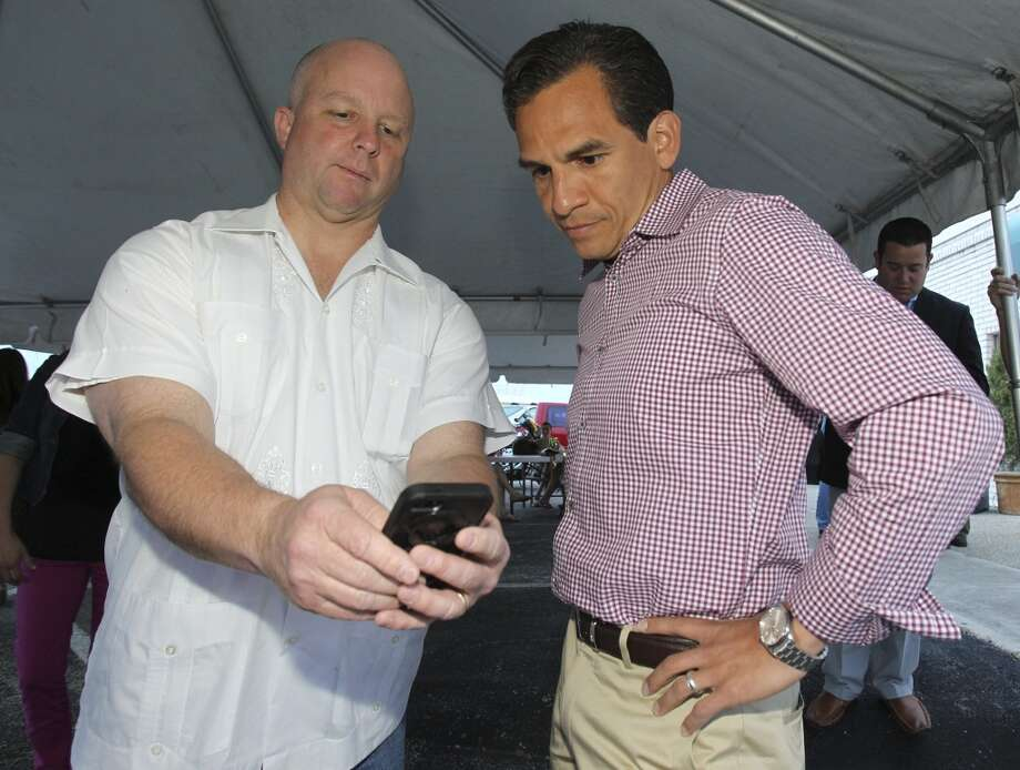 Rolando Briones takes a look at early results with Kevin Wolff at his election night party  on May 11, 2013.