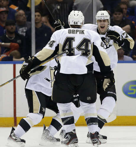 Penguins center Evgeni Malkin (right) rejoices with defenseman Brooks Orpik, who scored the winning goal in overtime of Game 6 to oust the Islanders from the playoffs. Photo: Kathy Willens / Associated Press