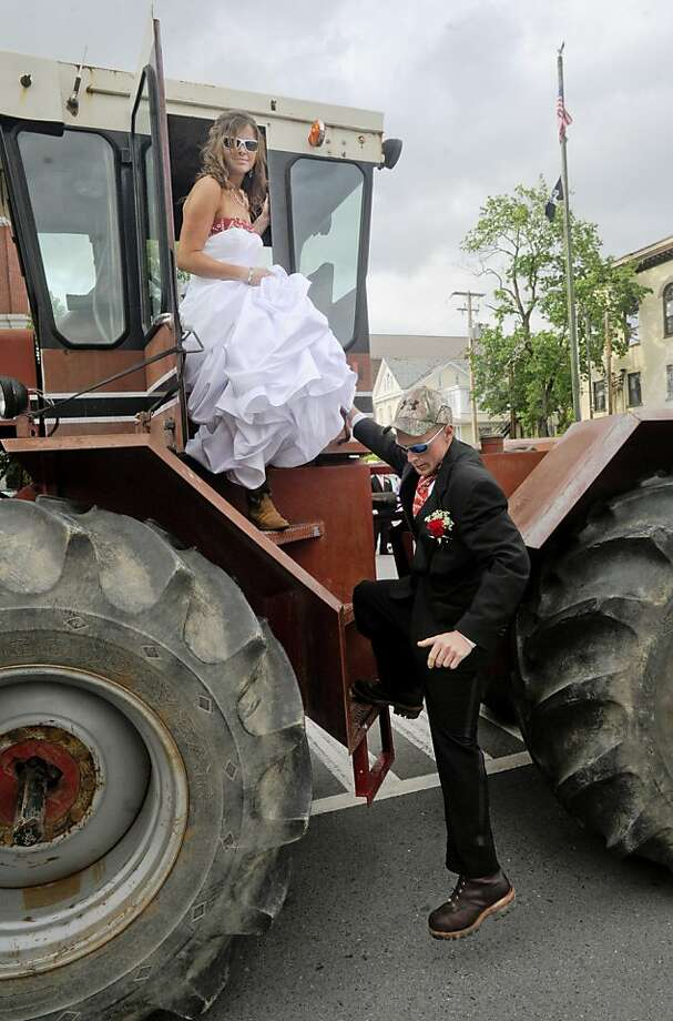 Renee Kozer, of Danville, climbs down from her family's 4386 International Harvester tractor after her boyfriend Ricky Long, of Berwick, after Kozer drove the couple to Columbia-Montour Vo-Tech's prom at the Caldwell Consistory in Bloomsburg in the tractor, Saturday evening, May 11, 2013 in Bloomsburg Pa.  Photo: Jimmy May, Associated Press
