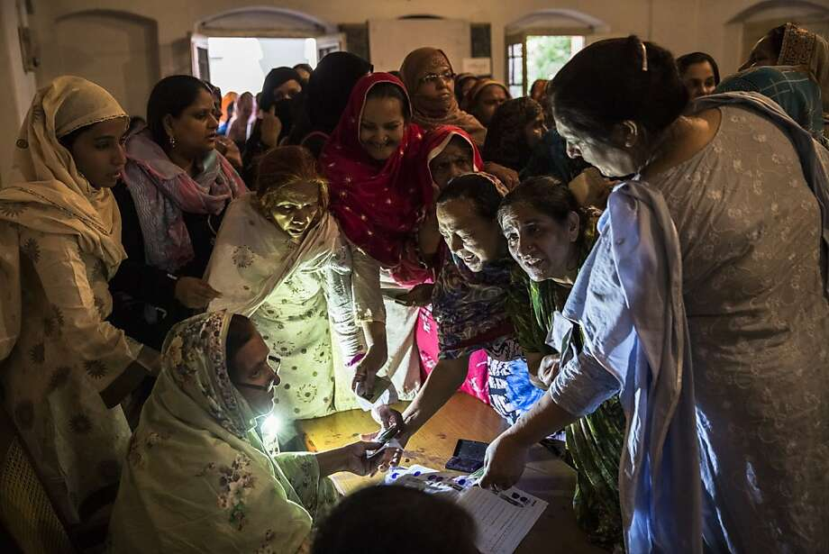 Pakistani women jostle to receive their ballot papers prior to casting their ballot at a polling station on May 11, 2013 in the Old City of Lahore, Pakistan. Millions of Pakistanis cast their votes in parliamentary elections held today on May 11. It is the first time in the country's history that an elected government will hand over power to another elected government.  Photo: Daniel Berehulak, Getty Images
