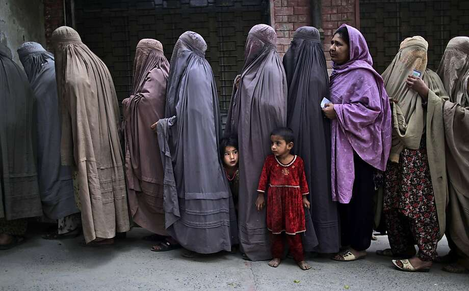 Pakistani women line up to enter a polling station and cast their ballots, on the outskirts of Islamabad, Pakistan, Saturday, May 11, 2013. Pakistanis streamed to the polls Saturday to vote in a historic election pitting a cricket star-turned-politician against an unpopular incumbent and a two-time prime minister, but twin bombings killing nine people and wounding dozens underlined the dangers voters face.  Photo: Muhammed Muheisen, Associated Press