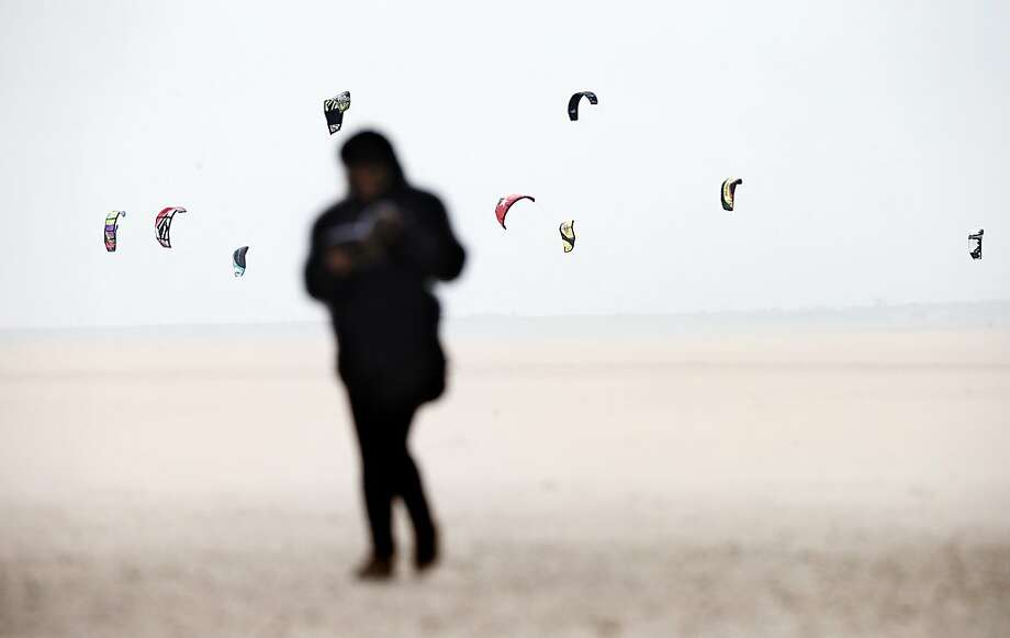 A person walks on the beach as kite surfers enjoy the strong southwest wind, in Maasvlakte, the Netherlands, on May 10, 2013. In the coming days the nice weather will be disturbed by clouds and rain.  Photo: Jerry Lampen, AFP/Getty Images