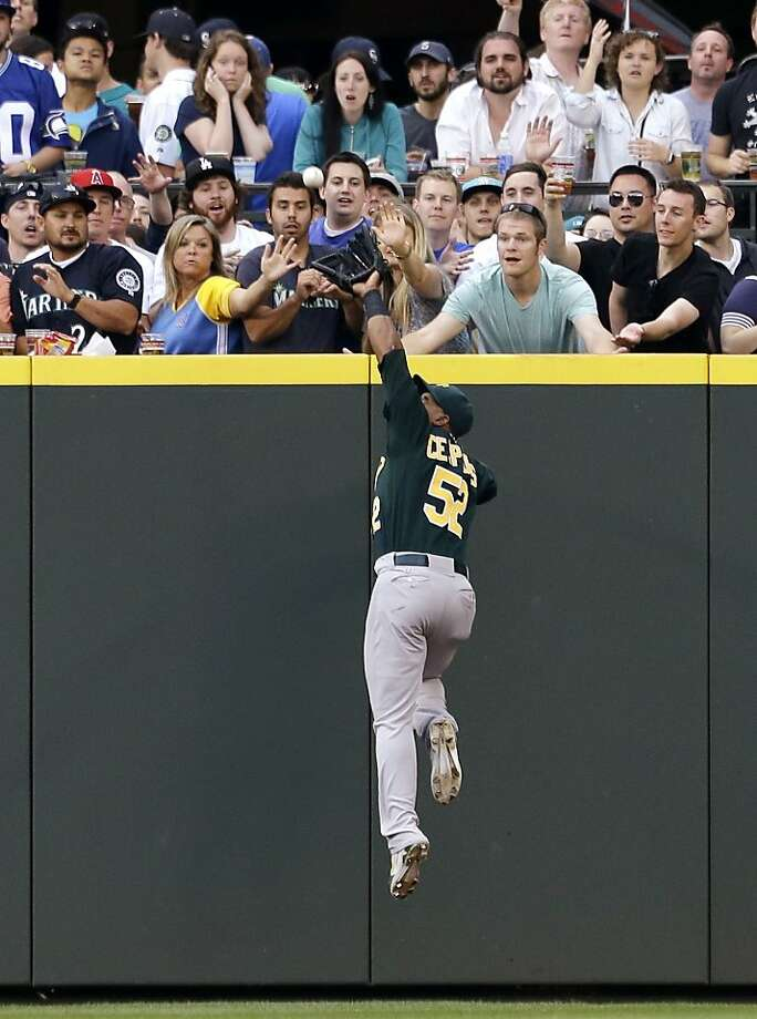 A's center fielder Yoenis Céspedes robs Kyle Seager of a homer in the sixth. Photo: Elaine Thompson, Associated Press
