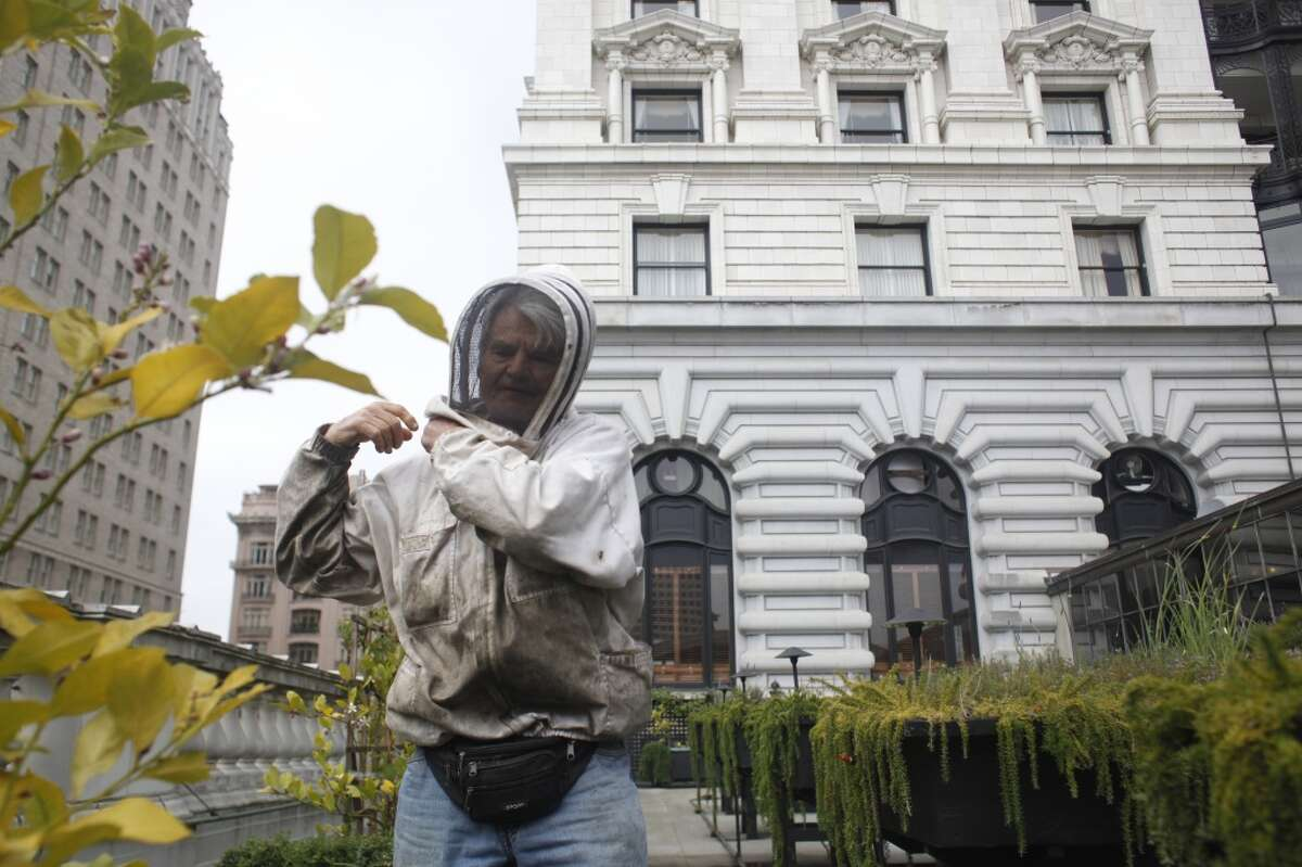 Master beekeeper Spencer Marshall zips up his bee suit before tending to four double queen beehives on the roof of the Fairmont Hotel in San Francisco.