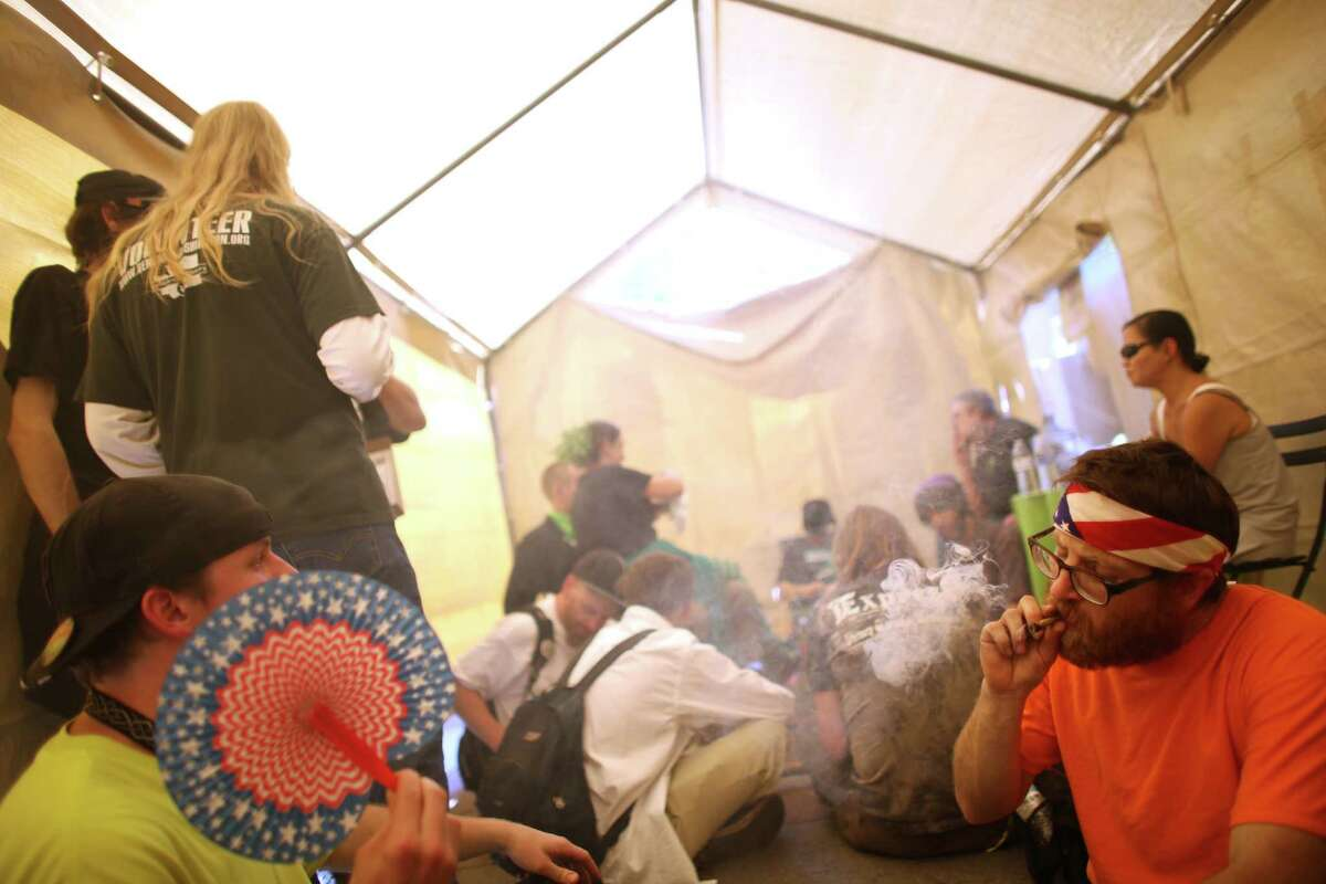 People gather in an enclosed and legal smoking tent at Westlake park during the Cannabis Freedom March and