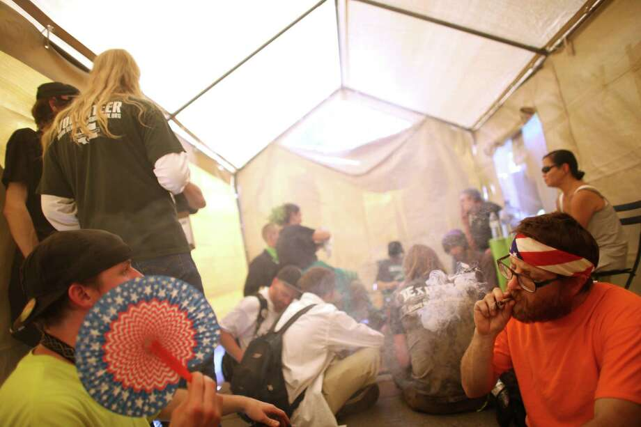 "People gather in an enclosed and legal smoking tent at Westlake park during the Cannabis Freedom March and ""prohibition funeral"" celebrating the legalization of marijuana in Washington State. Participants were also demanding more freedom for pot smokers and growers and an end to prohibition at a federal level. Photographed Saturday, May 11, 2013 in Seattle. Photo: JOSHUA TRUJILLO, SEATTLEPI.COM / SEATTLEPI.COM"