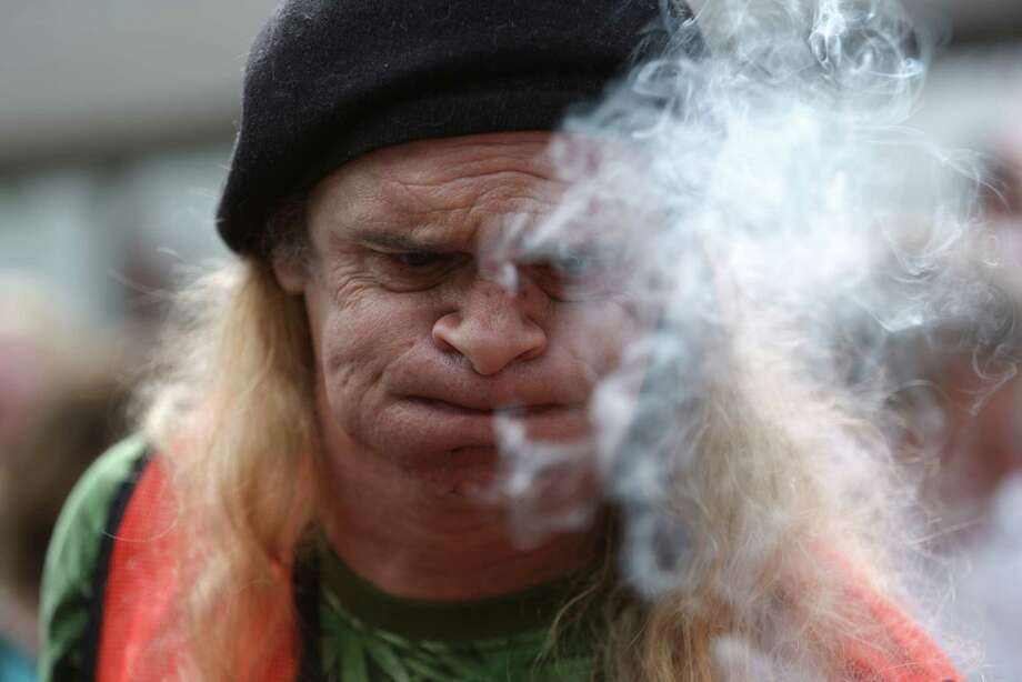 "A man who gave his name as ""John The Freak"" exhales marijuana smoke at Westlake Park. Photo: JOSHUA TRUJILLO, SEATTLEPI.COM / SEATTLEPI.COM"