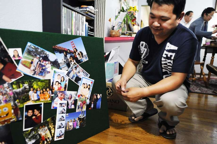 "Aldrin Geronga looks at a collage of family photos that will be used at the memorial service for his wife, Felomina ""Fyla"" Geronga, at the family's home Alameda, CA Wednesday May 8th, 2013."