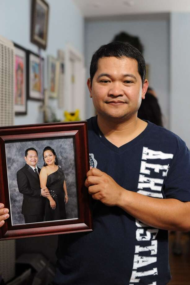 "Aldrin Geronga holds a picture of he and his wife, Felomina ""Fyla"" Geronga, at the family's home Alameda, CA Wednesday May 8th, 2013."