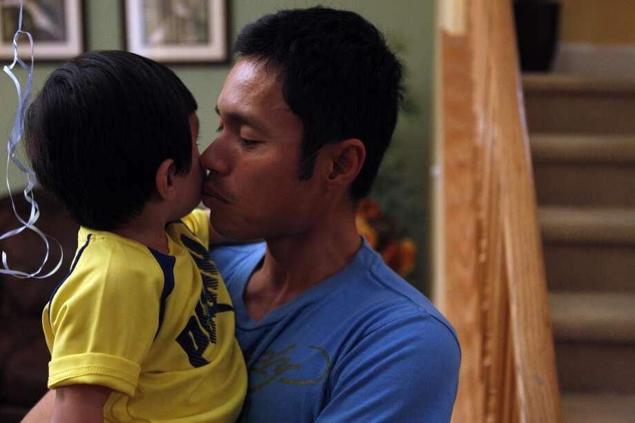 John Balon kisses his son, Jayden 22 mos., as he speaks to the media in his Dublin, Calif., home  on Monday, May 6, 2013, about his wife Jenni Balon and her death in a limousine fire on Saturday.