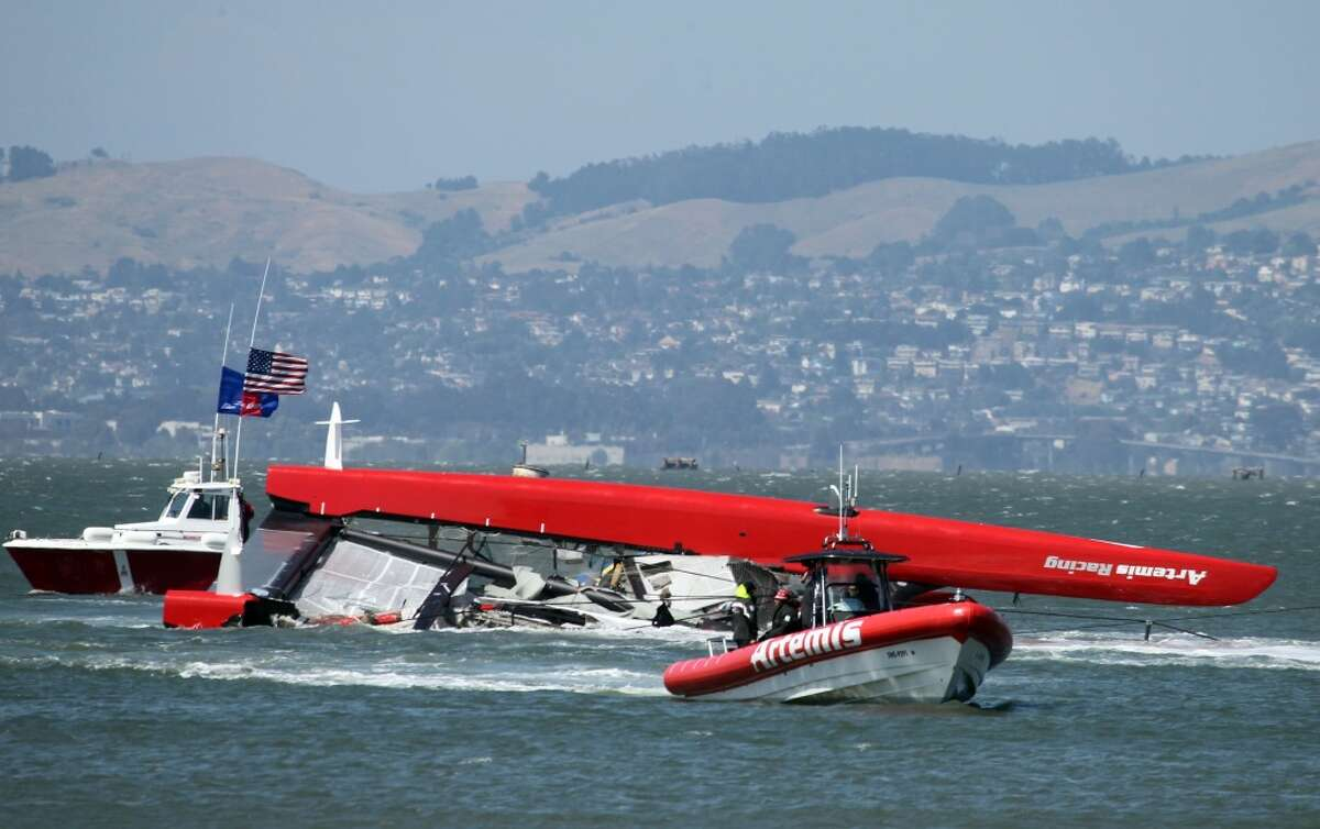Artemis support boats pull the 72-foot long catamaran that capsized in San Francisco Bay, killing one crewmember back to the Swedish teams port on Treasure Island Thursday May 9, 2013.