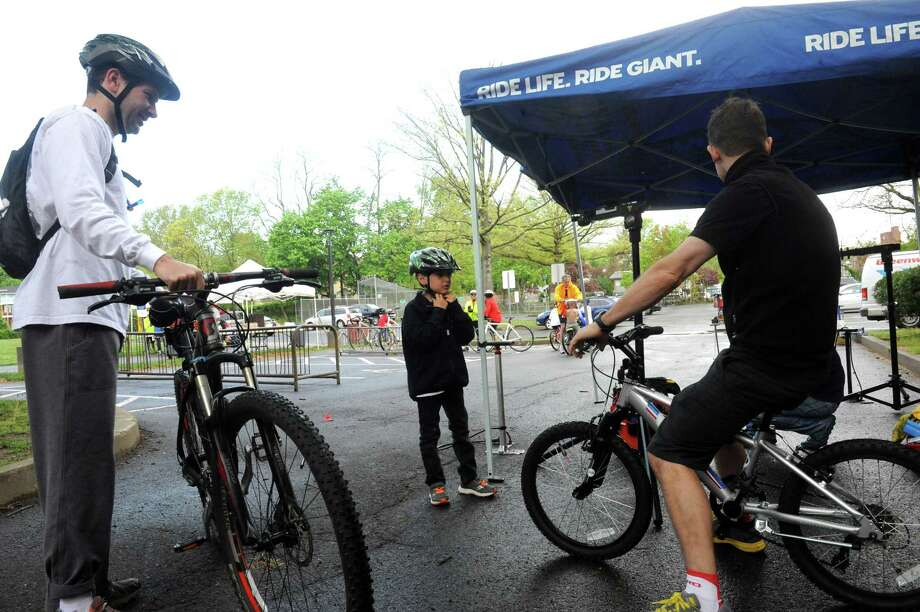 Jeff Toback, of Old Greenwich, and son, Zach,7, watches Peter Preston of Dave's Cycle tighten their bikes at Greenwich Safe Cycling's clelebration for Mother's Day and National Bike Month, Sunday, May 12, 2013. The event starts at Old Greenwich School and goes around Greenwich Point. Photo: Helen Neafsey / Greenwich Time