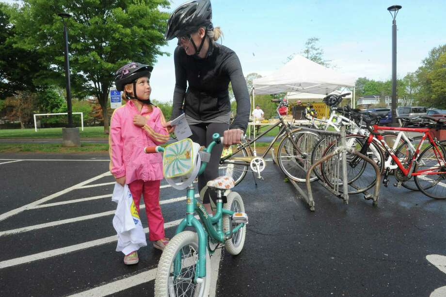 Carolyn Van Hell, 6, and her mother Liz, of Greenwich, gets ready for the Greenwich Safe Cycling's clelebration for Mother's Day and National Bike Month, Sunday, May 12, 2013. The event starts at Old Greenwich School and goes around Greenwich Point. Photo: Helen Neafsey / Greenwich Time
