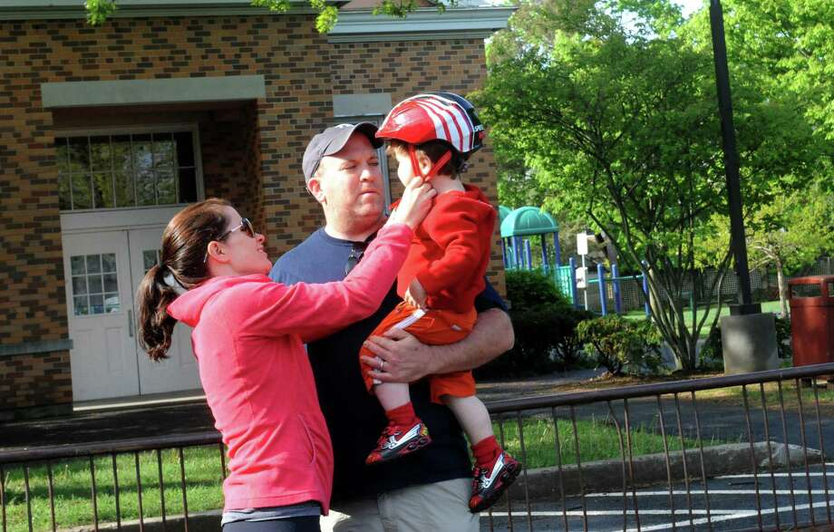 From left: Lindsay O'Brien, of Riverside, her husband Terry hold Colin, 2, get ready for the Greenwich Safe Cycling's clelebration for Mother's Day and National Bike Month, Sunday, May 12, 2013. The event starts at Old Greenwich School and goes around Greenwich Point. Photo: Helen Neafsey / Greenwich Time