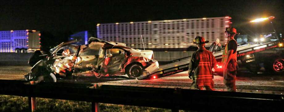 Rockdale, Ga. firefighters look on as wreckage from the scene is loaded on a tow truck early Friday, May 10, 2013.  Georgia State Patrol officials say two people, including a baby, were killed in an early morning street racing crash. Authorities say the baby's unidentified mother was racing her Honda accord on I-20 early Friday morning in Rockdale County and lost control of the car. The car hit a guardrail and was eventually hit by a pickup truck. (AP Photo/Atlanta Journal-Constitution, John Spink)  Photo: AP