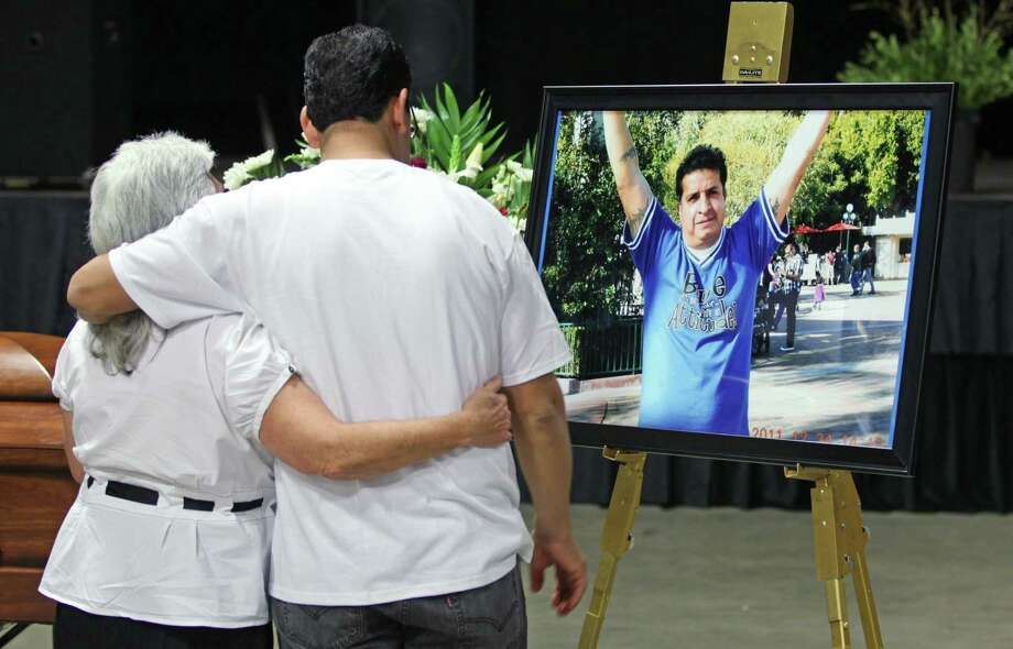Marco Martinez, right, and Bea Manzanares pay thier respects to Ricardo Portillo during a public wake Wednesday, May 8, 2013, in Salt Lake City. People attended the wake to honor the Utah soccer referee who was punched by a player and later died after a weeklong coma. Photo: AP