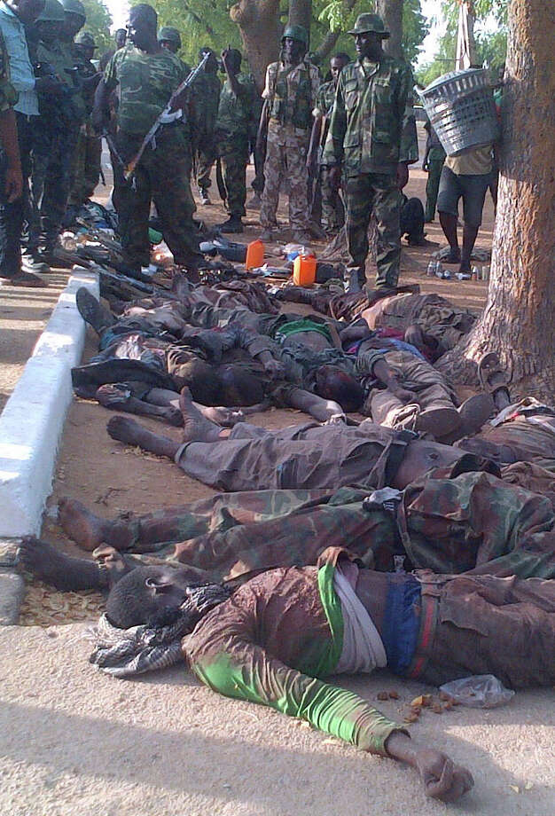 In this photo taken with a mobile phone, Tuesday, May. 7, 2013, soldiers looks at bodies of suspected Islamic extremist killed during  heavy fighting in Bama, Nigeria. Coordinated attacks by Islamic extremists armed with heavy machine guns killed at least 42 people in northeast Nigeria, authorities said Tuesday, the latest in a string of increasingly bloody attacks threatening peace in Africa's most populous nation. The attack struck multiple locations in the hard-hit town of Bama in Nigeria's Borno state, where shootings and bombings have continued unstopped since an insurgency began there in 2010. Fighters raided a federal prison during their assault as well, freeing 105 inmates in another mass prison break to hit the country, officials said. Photo: AP