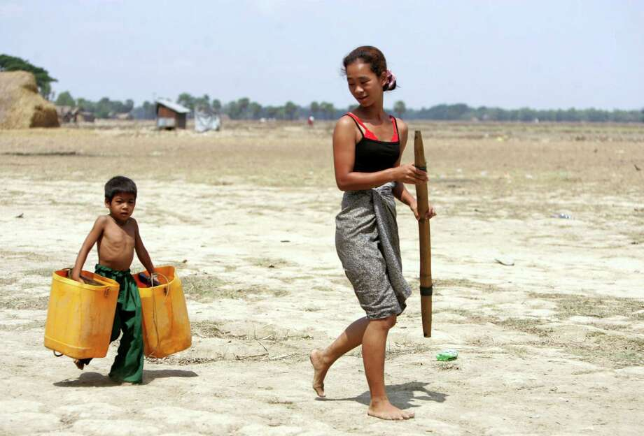A boy carrying empty plastic containers follows his mother to help her fetch water, in Dala township, about 15 kilometers (9 miles) south of Yangon, Myanmar, Tuesday, May 7, 2013. Several regions and states in Myanmar face acute water shortage especially in the summer. Dala, located opposite of Yangon faces severe water shortage all year round except during the rainy seasons which begins in May until mid-October. Photo: AP