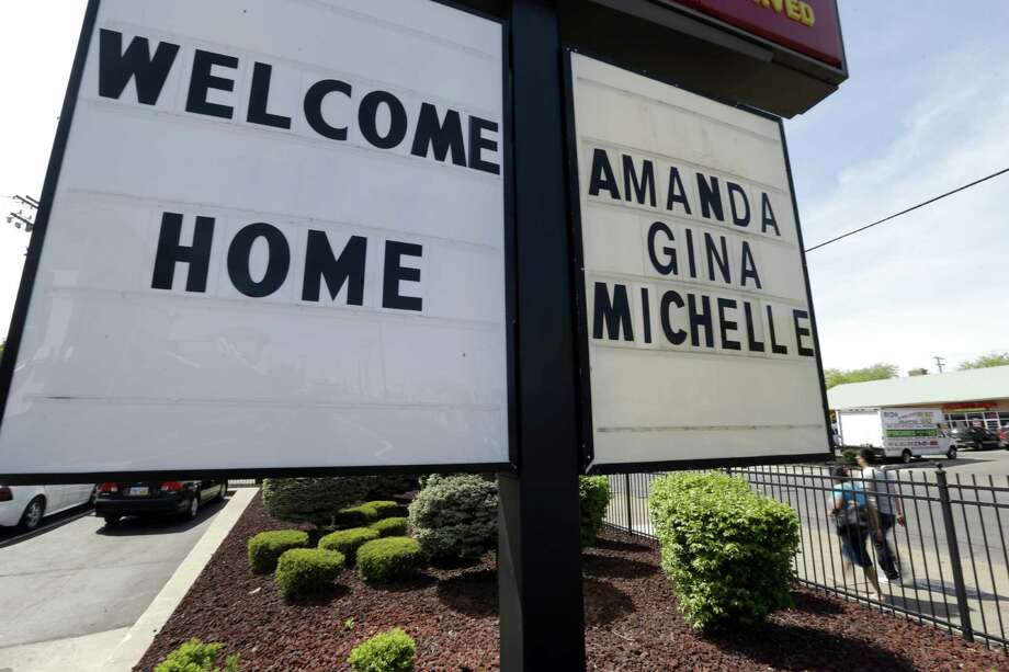 "In this Thursday, May 9, 2013 file photo, a ""Welcome Home"" sign is posted at a restaurant near a crime scene where three women were held captive for a decade in Cleveland. For Gina DeJesus, Amanda Berry and Michelle Knight, who were freed from captivity inside a Cleveland house Monday, May 6, 2013, the ordeal is not over. Next comes recovery _ from sexual abuse and their sudden, jarring reentry into a world much different than the one they were snatched from a decade ago. Photo: AP"